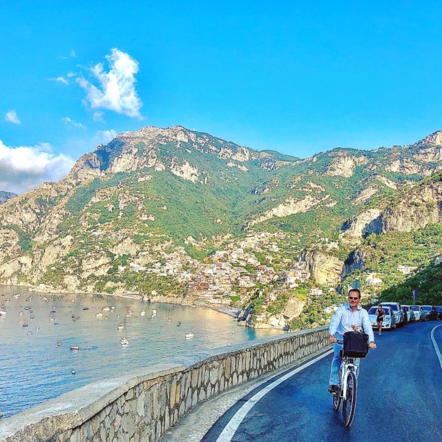 Mela catches a ride to work with Vito on his electric bike; their favorite way to commute to and from the San Pietro.#ecofriendlyliving #ilsanpietrodipositano #melathesuperjack #relaischateaux #positano #amalficoast